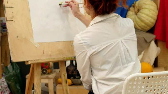 Female artist working on watercolor painting in studio video