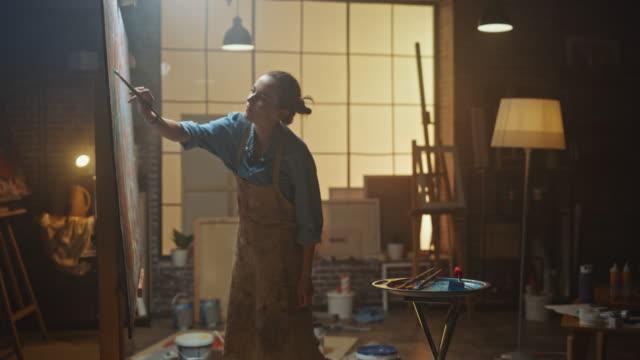 weibliche künstlerin arbeitet auf abstrakte ölgemälde, moving paint brush energetisch schafft sie moderne meisterwerk. dunkles kreativstudio, in dem große leinwand auf easel beleuchtet steht. zoom in shot - gemälde stock-videos und b-roll-filmmaterial