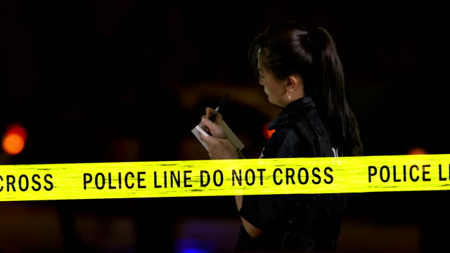 Female Asian American policewoman taking notes at crime scene with flashing police car siren in background video