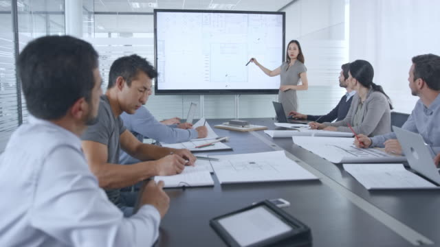 female asian architect presenting the plans on a large screen in the conference room - leanincollection stock videos & royalty-free footage