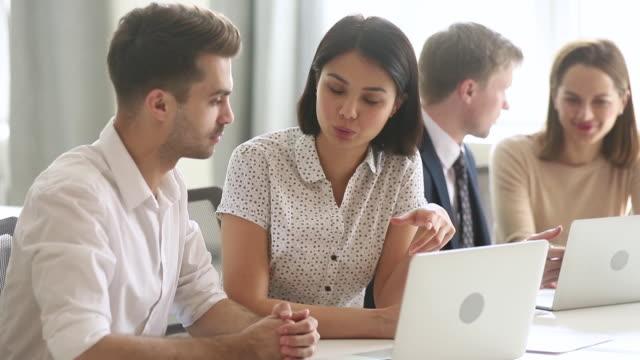 Female asian mentor teaching male caucasian intern explaining online strategy