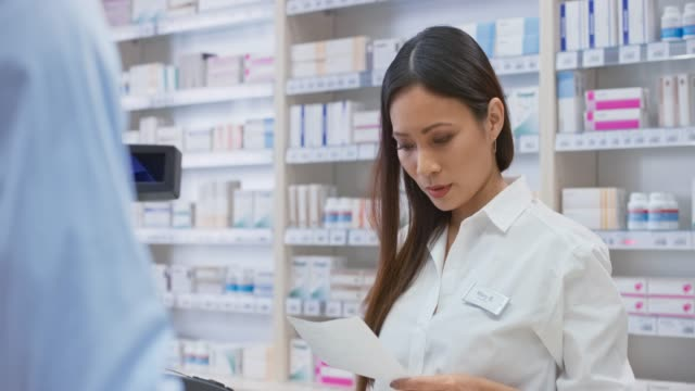 Female Asian pharmacists taking a look at the prescription and getting the medicine