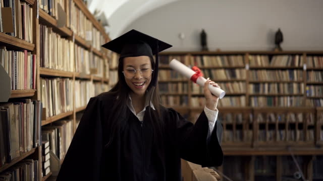 Female asian student lawyer in roung glasses and black gown holding Female asian student lawyer in roung glasses and black gown holding scroll in her hand and enjoying her graduation in the library. Indoors. Portrait. diploma stock videos & royalty-free footage