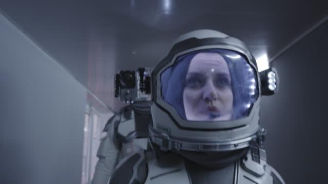 weibliche astronautin, die einen korridor hinuntergeht - raumanzug stock-videos und b-roll-filmmaterial