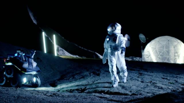 Mujer astronauta caminando por el planeta alienígena mirando a su alrededor con asombro. En los cuartos de estar de fondo. Viajes espaciales, exploración interestelar y concepto de colonización del Sistema Solar. - vídeo