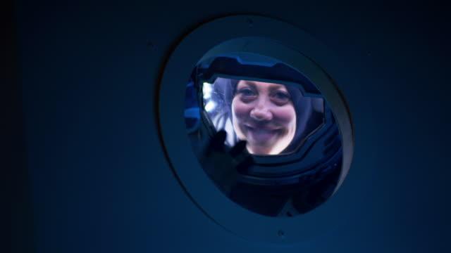 weibliche astronautin winkt vor der kamera vom raumschiff - raumanzug stock-videos und b-roll-filmmaterial