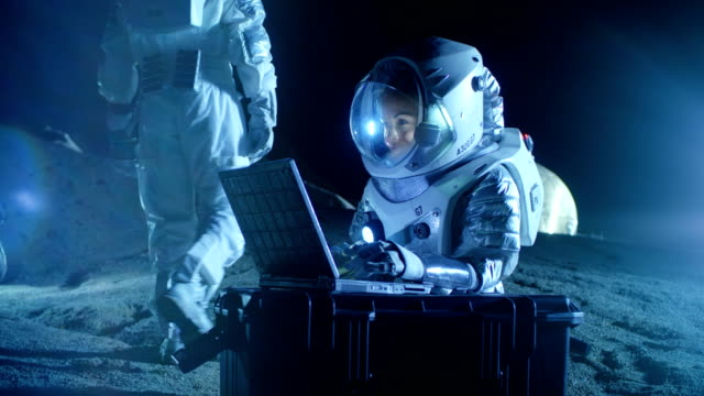 Female Astronaut Wearing Space Suit Works on a Laptop, Exploring Newly Discovered Planet, Communicating with the Earth. In the Background Her Crew Member and Space Habitat. Colonization Concept. video