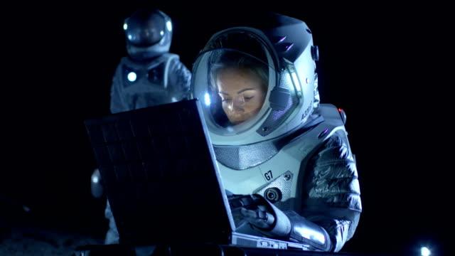 Mujer astronauta con traje espacial trabaja en un portátil, explorando nuevamente había descubierto planeta, comunicarse con la tierra. En el fondo su miembro de la tripulación y la estación de la vida. Concepto de colonización extraterrestre. - vídeo