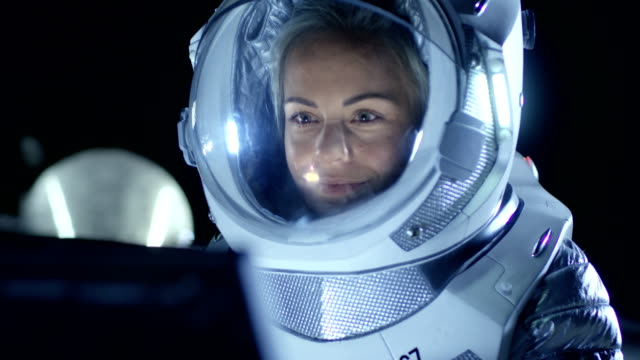 Female Astronaut Wearing Space Suit Works on a Laptop, Exploring Newly Discovered Planet, Communicating with the Earth. In the Background Living Station. Colonization Concept. video