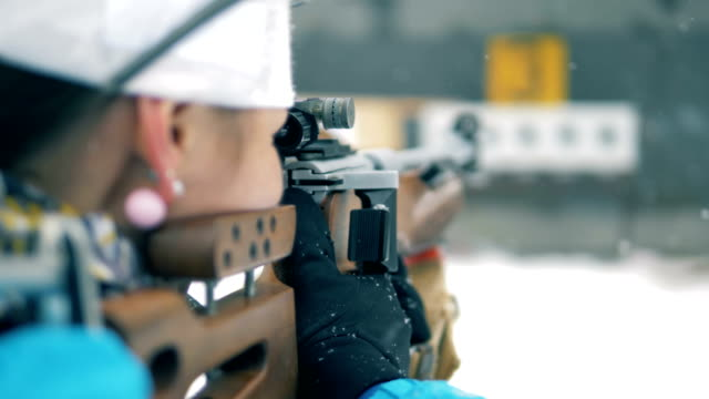 female athlete aiming with rifle, close up. - taking a shot sport stock videos & royalty-free footage