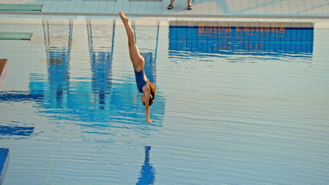 SLO MO Female athlete diving from a high platform at a competition