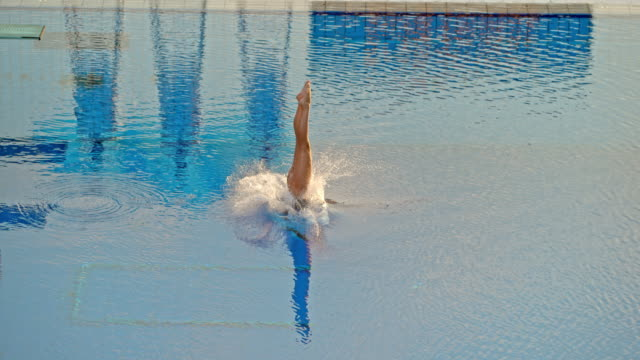 slo mo female athlete diving from a high platform in a competition - tuffarsi video stock e b–roll