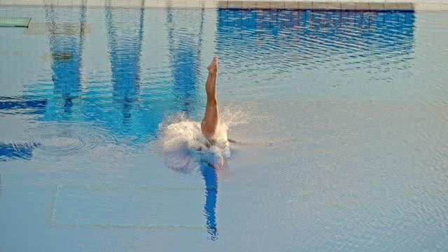 vidéos et rushes de slo mo athlète plongée depuis une plate-forme élevée lors d'un concours - perfection