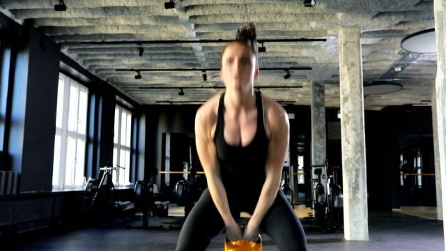 vidéos et rushes de athlète féminine faisant kettlebell swings dans la salle de gym - décolleté