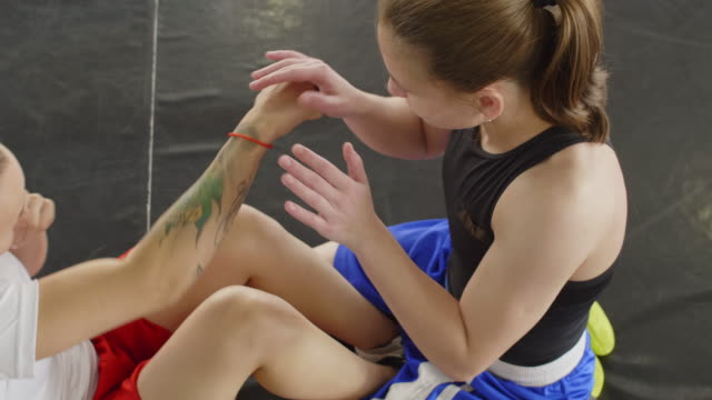 Female Athlete Doing Punching Sit Ups with Help of Partner on Boxing Ring