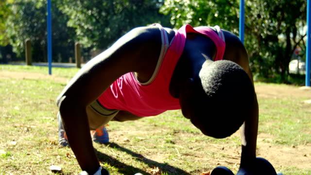 女性アスリートのプッシュを行う公園 4 k アップ - 女性選手点の映像素材/bロール