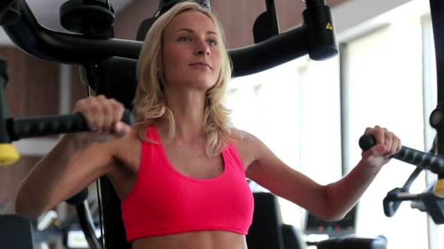 Female athlete doing seated front press on machine in gym indoors video