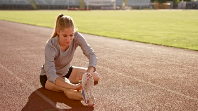 SLO MO Female athlete doing stretching exercises sitting on the track in the stadium