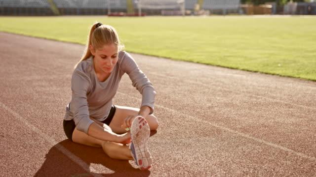 slo mo female athlete doing stretching exercises sitting on the track in the stadium - rozciągać filmów i materiałów b-roll