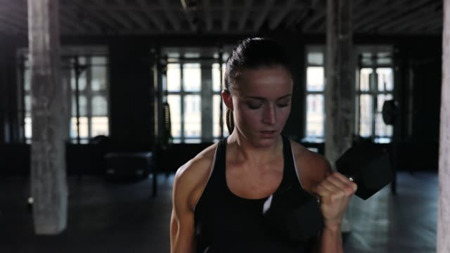 Female athlete exercising with dumbbells in gym