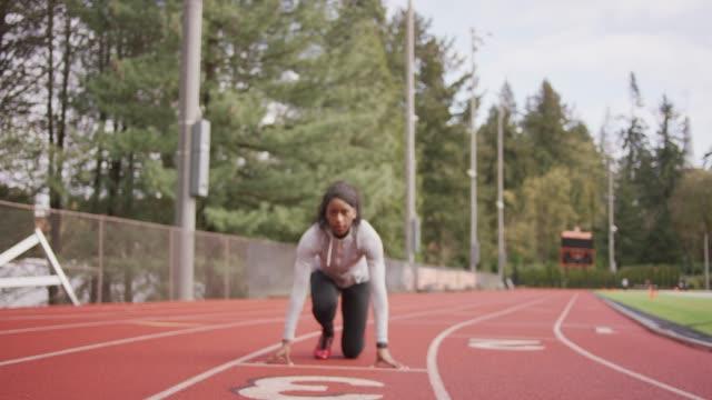 vidéos et rushes de athlète féminine dans une position de départ pour le sprint - starting block