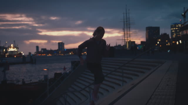 vídeos de stock e filmes b-roll de female athlete jogging up on staircase at harbor - young woman running city