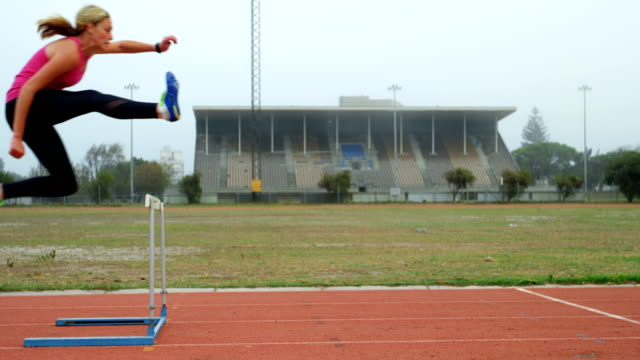 Female athlete jumping over hurdles on a running track 4k