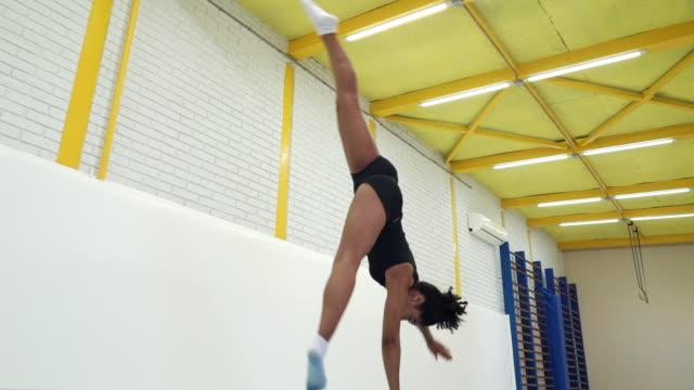 vídeos de stock, filmes e b-roll de atleta feminina fazendo exercício de roda de carroça em tapetes na academia - ginástica