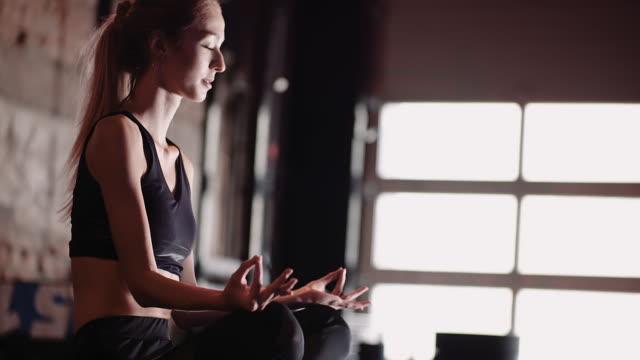 female athlete mediterar på health club - korslagda ben bildbanksvideor och videomaterial från bakom kulisserna