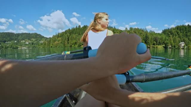 pov sportlerin bewegt sich in einem doppelzweier beim rudern hinter ihrer teamkollegin - sportrudern stock-videos und b-roll-filmmaterial
