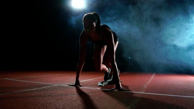 kadın atlet karanlık bir arka plan üzerinde koyu arka plan üzerinde treadmill yastıkları arazi sprint çalıştırılmaya hazırlanıyor - başlama çizgisi stok videoları ve detay görüntü çekimi