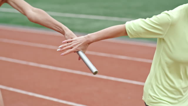 Female athlete passing baton in relay race - vídeo