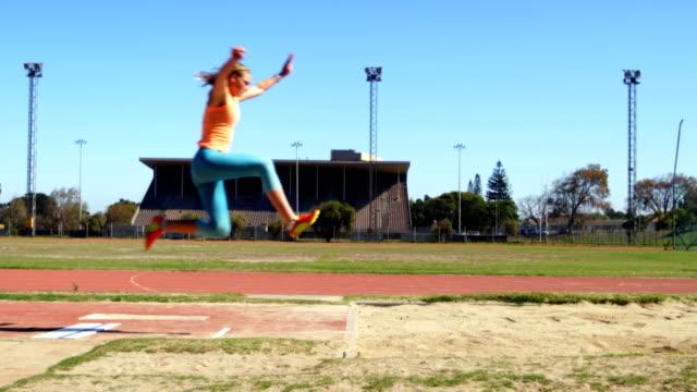 vídeos y material grabado en eventos de stock de atleta femenina practicando salto de longitud en lugar de deportes 4k - largo longitud