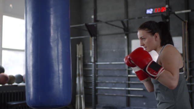 Female Athlete Punching the Bag in Boxing Gym