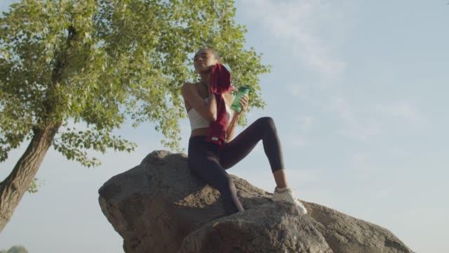 kvinnlig idrottsman vilar efter löpning motion - black woman towel workout bildbanksvideor och videomaterial från bakom kulisserna