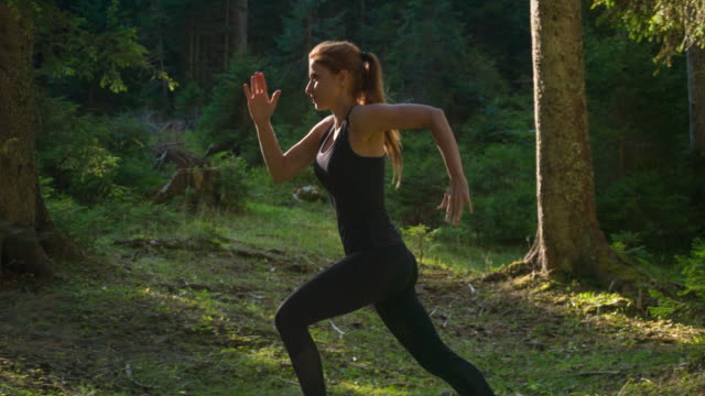 female athlete running in the woods - agilità video stock e b–roll