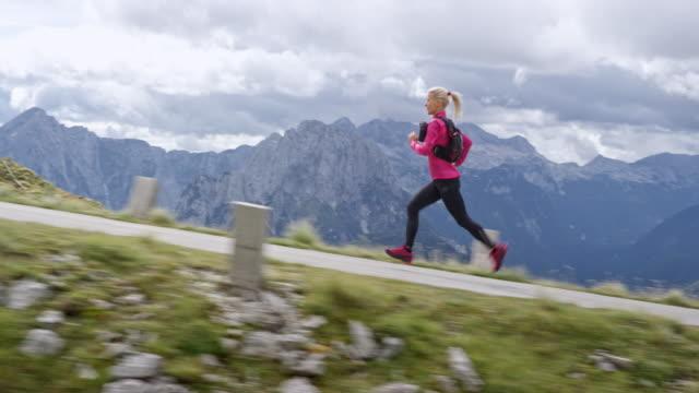 日差しの中で高い山の道の上実行している slo mo ts 女性アスリート - 有酸素運動点の映像素材/bロール