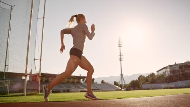güneşli stadyumda yolda çalışan slo mo ts kadın atlet - pist stok videoları ve detay görüntü çekimi