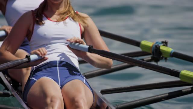 vídeos de stock, filmes e b-roll de atleta feminina lemada com companheiro de equipe em um double scull em um dia ensolarado - remo atividade física