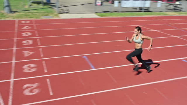 female athlete sprinting to finish line on sports track - reggiseno sportivo video stock e b–roll