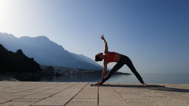 Female athlete standing in yoga poses in beautiful seascape