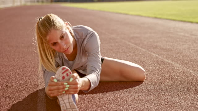 SLO MO Female athlete stretching her legs while sitting on the track in the stadium video