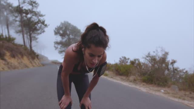 vídeos de stock e filmes b-roll de female athlete taking breath from running - dureza
