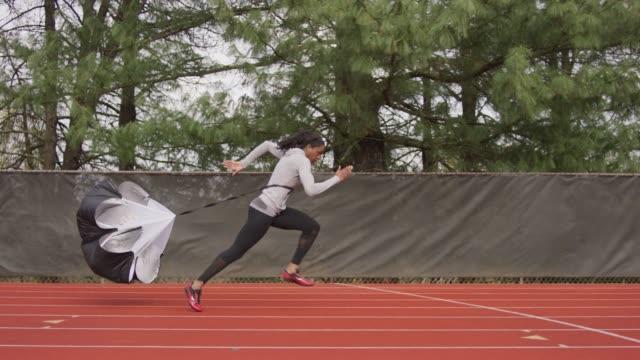 kadın atlet eğitim bir paraşüt ile - pist stok videoları ve detay görüntü çekimi