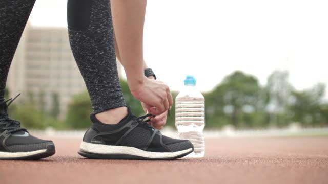 atleta femminile legare su scarpa sportiva - annodare video stock e b–roll