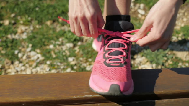 Female athlete tying pink sports shoe video