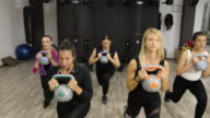 istock Female athletes doing lunges with kettlebell during weight class at gym 1251631189