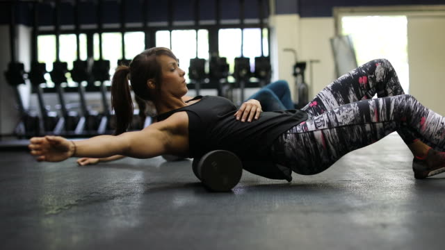 female athletes exercising on foam rollers in gym - rotolare video stock e b–roll