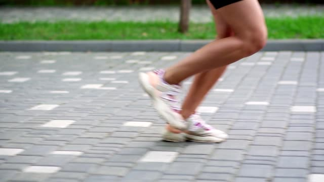 female athlete's feet running at the park. fitness woman jogging outdoors. exercising on park pavement. healthy, fitness, wellness lifestyle. sport, cardio, workout concept. side view. slow motion - pantaloncini video stock e b–roll