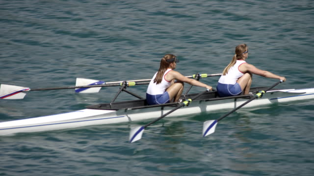 Female athletes sculling across a sunny lake in a double scull